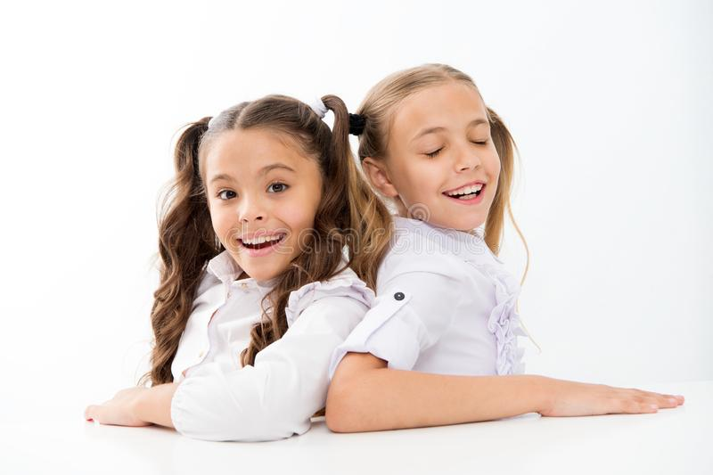 Happy childhood. Adorable schoolgirls. Back to school. Education concept. Beautiful girls best friends. Formal style. Schoolgirls sit at desk white background royalty free stock image