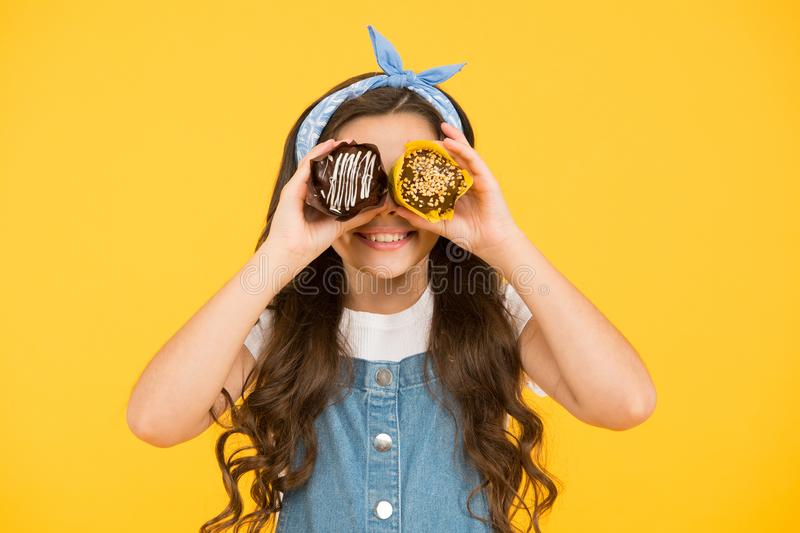 Happy childhood. Adorable smiling child with cupcakes on yellow background. Treat someone with sweets. Yummy cupcakes royalty free stock photos