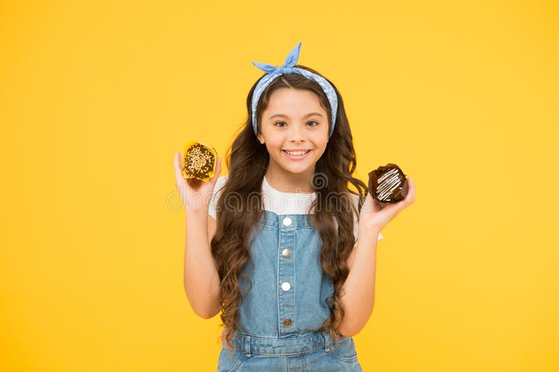Happy childhood. Bakery confectionery concept. Kid girl hold glazed muffins. Delicious cupcakes. Adorable smiling child. With cupcakes on yellow background stock photography