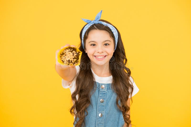 Happy childhood. Bakery confectionery concept. Kid girl hold muffin. Delicious cupcakes. Little child with muffin on. Yellow background. Treat someone with stock photography