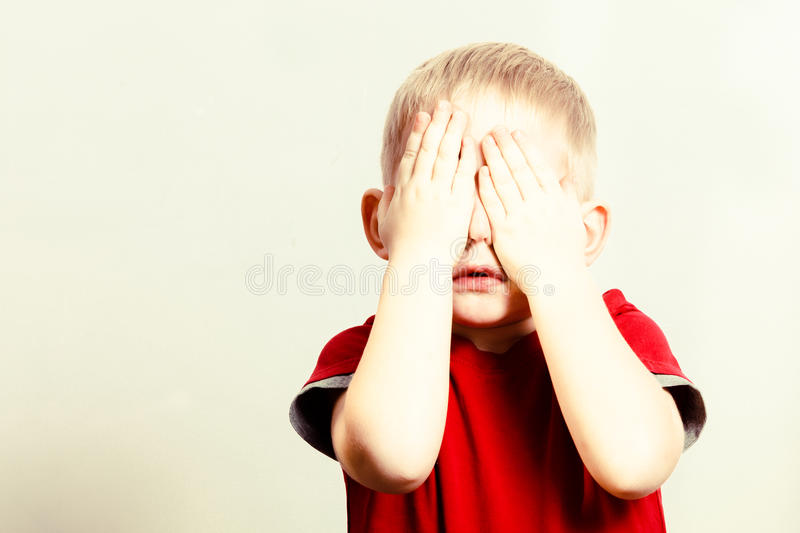 Happy childhood. Blond boy child kid covering face with hands stock image