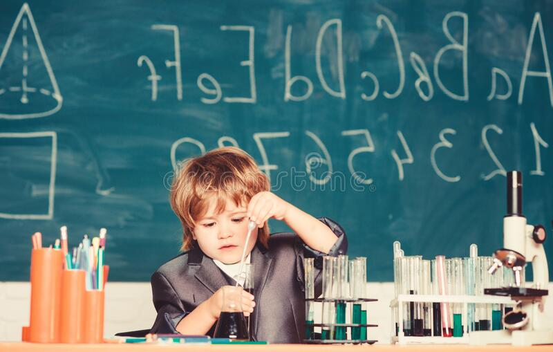 Happy childhood. Boy near microscope and test tubes school classroom. Knowledge concept. Knowledge day. Kid study stock photos