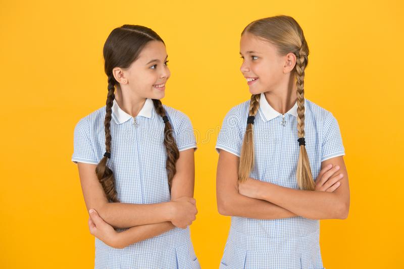 Happy childhood. brunette and blond hair. sisterhood concept. best friends. vintage style. small girls in retro uniform. Old school fashion. back to school royalty free stock photo