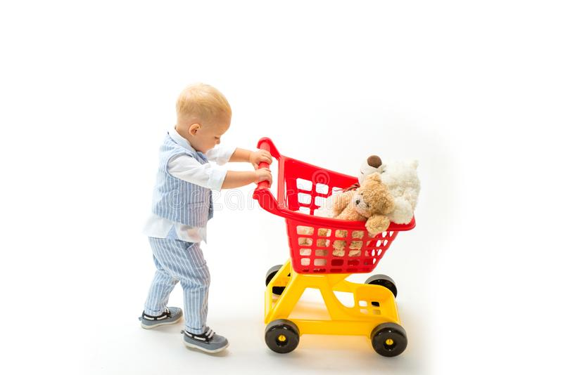 Happy childhood and care. shopping for children. little boy go shopping with full cart. savings on purchases. little boy stock photo