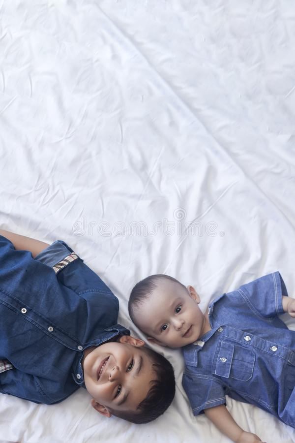 Happy childhood concept. Happy brothers portrait. 6 years boy and 6 months old baby boy having fun. Two little kids smiling to the. Camera. View from above stock images