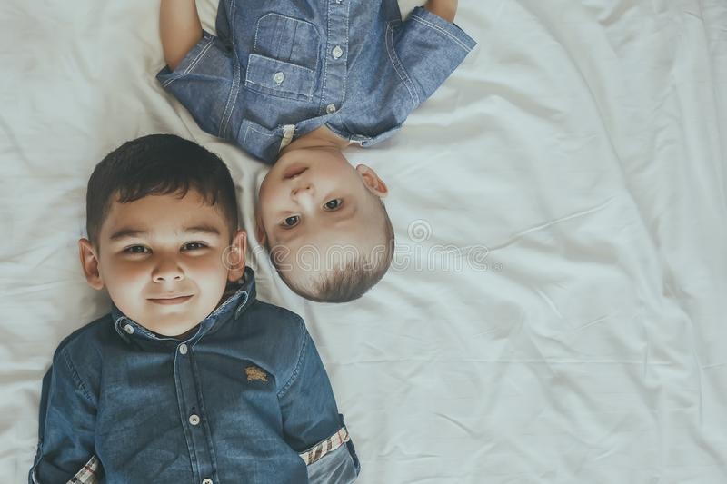 Happy childhood concept. Happy brothers portrait. 6 years boy and 6 months old baby boy having fun. Two little kids smiling to the. Camera. View from above royalty free stock photos