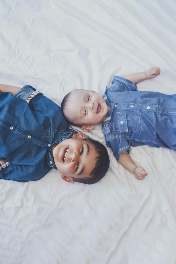 Happy childhood concept. Happy brothers portrait. 6 years boy and 6 months old baby boy having fun. Two little kids smiling to the. Camera. View from above royalty free stock images