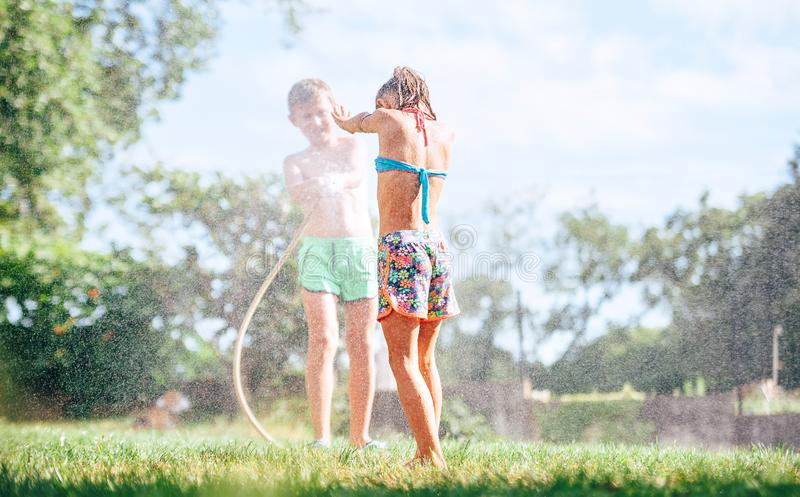 Happy childhood concept image.Two childs playing in garden, pours each other from the hose, makes a rain stock photo