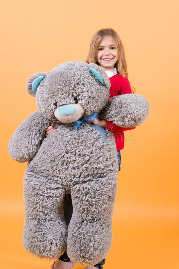 Happy childhood concept. Kid with animal doll, present and gift. Child smile with grey soft toy. Holiday, birthday, anniversary celebration. Girl hold big royalty free stock photos