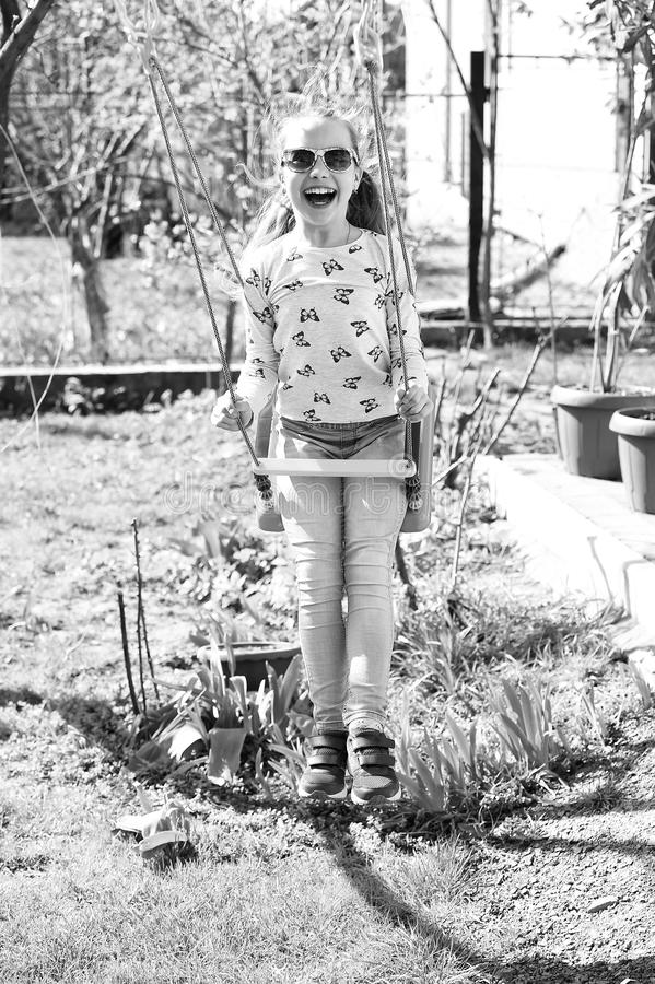 Happy childhood concept. Little child smile on swing in summer yard. Fashion girl in sunglasses enjoy swinging on sunny stock photos