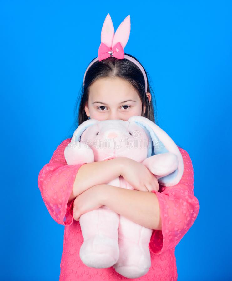 Happy childhood. Get in easter spirit. Bunny ears accessory. Lovely playful bunny child hugs soft toy. Have blessed stock photos