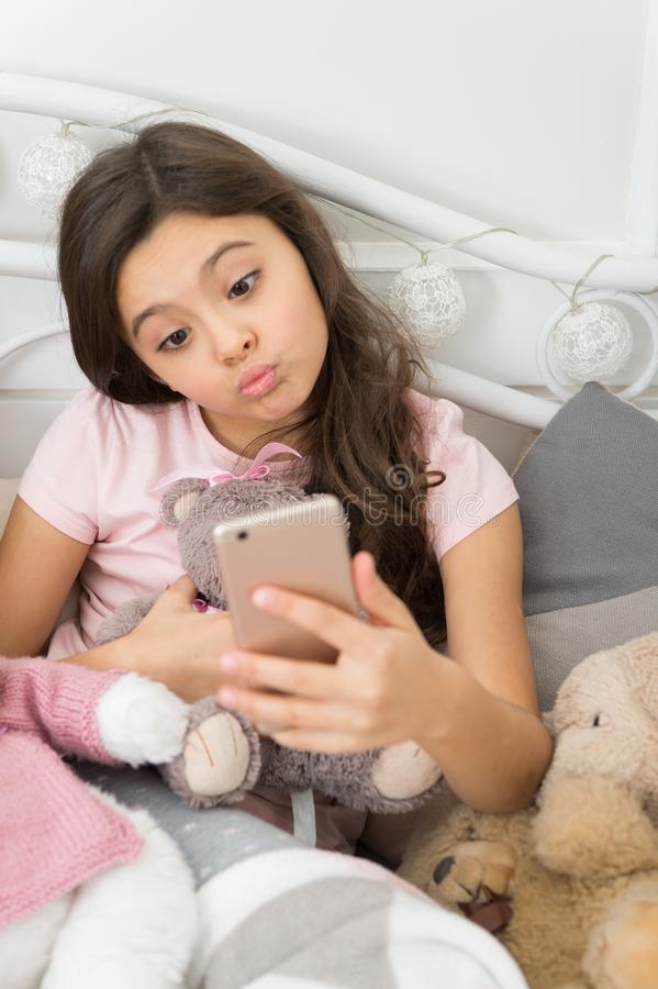 Happy childhood. Girl with smartphone use modern technology. Selfie with favorite toy. Send selfie photo your friends stock photo