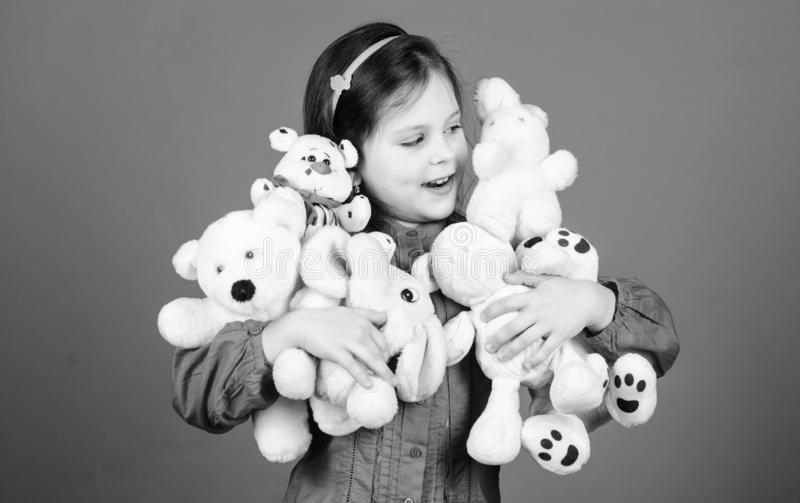 Happy childhood. Little girl play with soft toy teddy bear. Lot of toys in her hands. Childhood concept. Collecting toys stock images