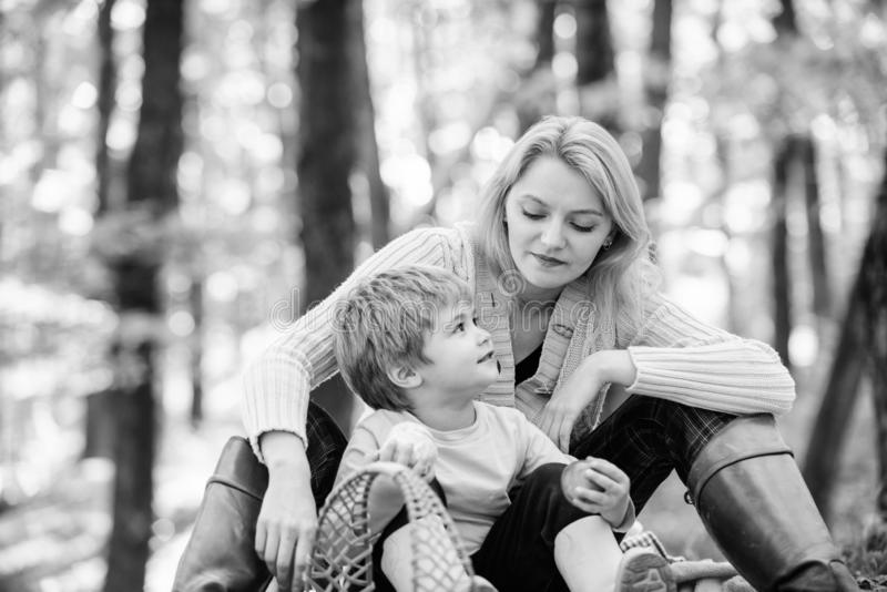 Happy childhood. Mom and kid boy relaxing while hiking forest. Family picnic. Mother pretty woman and little son royalty free stock image
