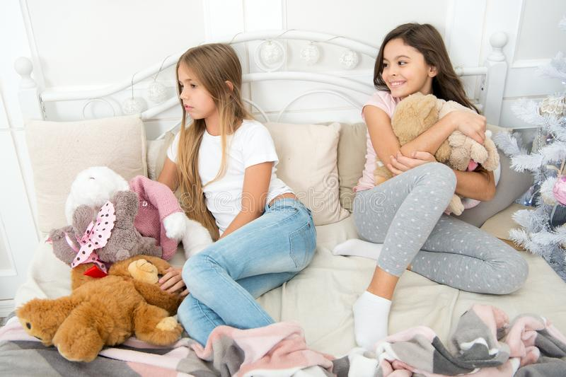 Happy childhood. Pajamas party. Sisters sharing toys. Sisters best friends. Kids play toys in bed. Little girls spend royalty free stock photos