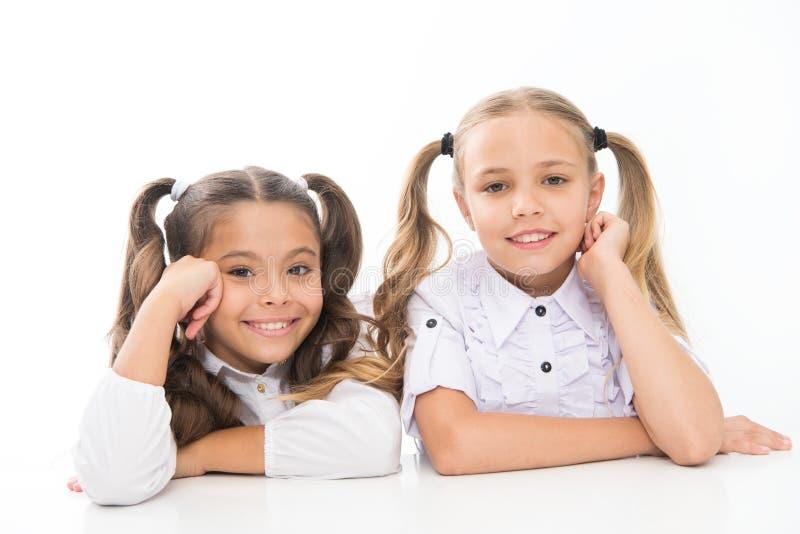 Happy childhood. Schoolgirls sit at desk white background. Schoolgirls emotional friends. Adorable schoolgirls. Back to stock photos