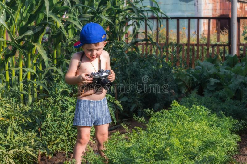 Happy childhood. Small baby is holding a camera and trying to take the photo at the garden. Little photographer royalty free stock photography
