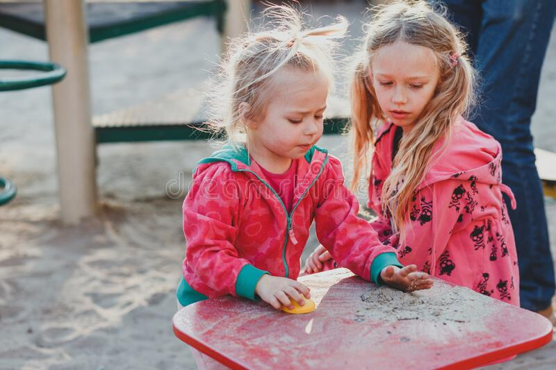 Two Little Girls Sisters Hugging And Having Fun In Park