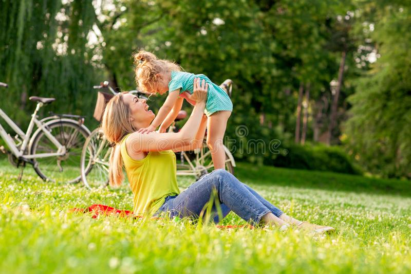 Happy Childhood - Young mother raising her girl child up royalty free stock images