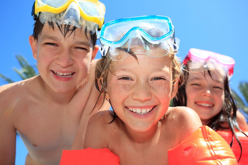 Happy children with goggles. Three happy, smiling children with swimming goggles royalty free stock photos