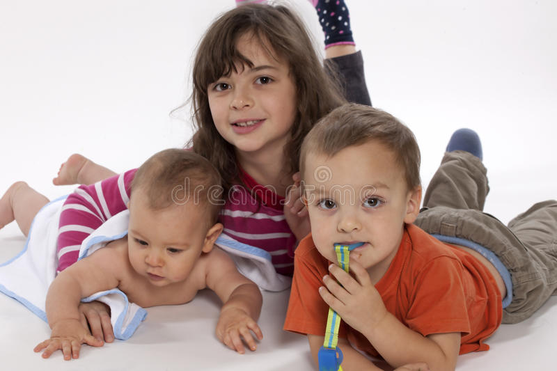 Happy children. Sister with brothers. White background stock photo