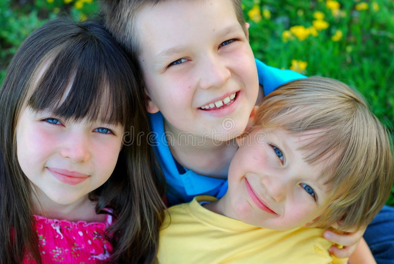Happy children. Three adorable smiling children; closeup portrait