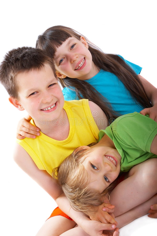 Happy children. Three happy children pose together, with the youngest boy lying on the older boy's lap