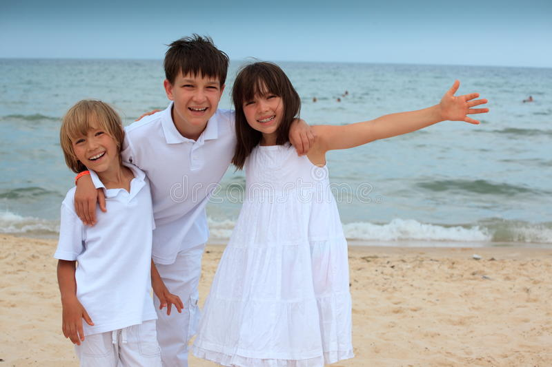 Happy children on beach. Sister with two brothers royalty free stock photography