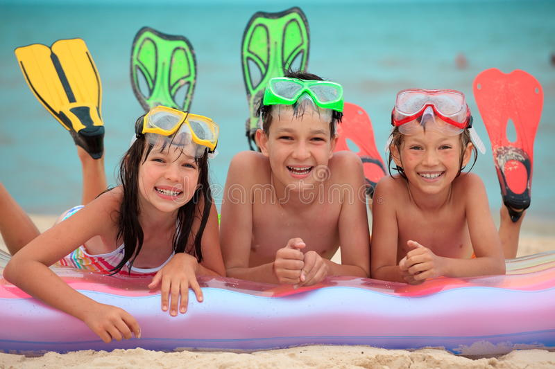 Happy children at beach. Three happy, smiling children on a beach with an inflatable mattress and swimming fins royalty free stock image