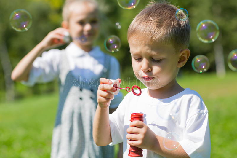 Happy children blow soap bubbles. On a bright sunny day. Brother and sister royalty free stock images