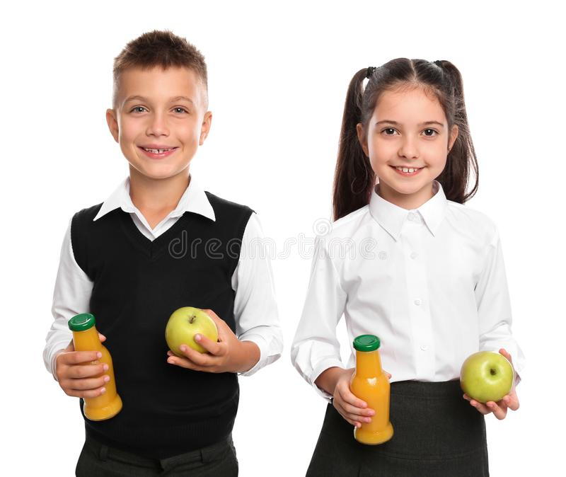Happy children with bottles of juice and apples. Healthy food for school lunch stock images