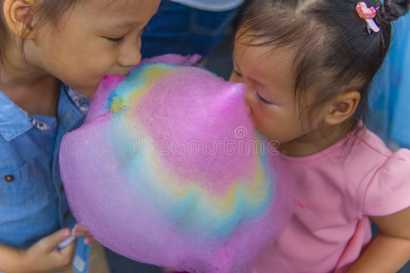Happy children boy and girl brother and sister eating cotton candy. High resolution image gallery stock images