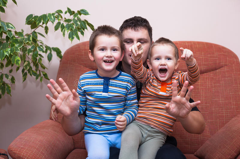 Happy children boys laughing with daddy. Happy children boys and daddy having fun on sofa at home royalty free stock photos