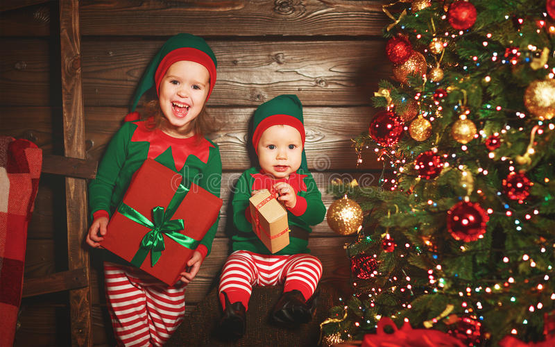Happy children brother and sister elf, helper of Santa with Christmas gifts. Happy children brother and sister elf, helper of Santa with a Christmas gifts royalty free stock photos