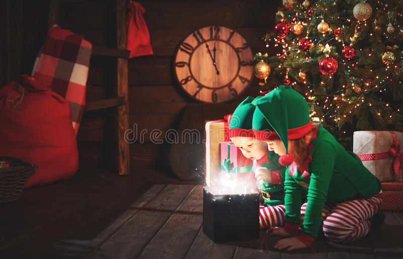 happy children brother and sister elf, helper of Santa with Christmas magic gifts stock images