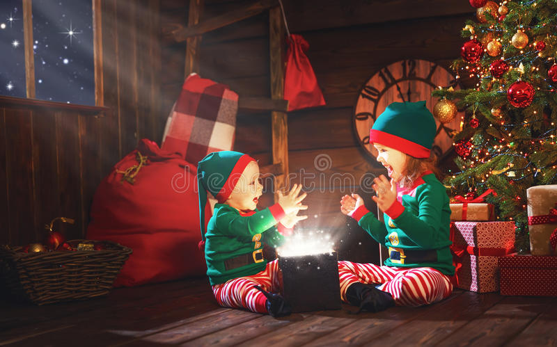 Happy children brother and sister elf, helper of Santa with Christmas magic gifts. Happy children brother and sister elf, helper of Santa with a Christmas magic royalty free stock photography