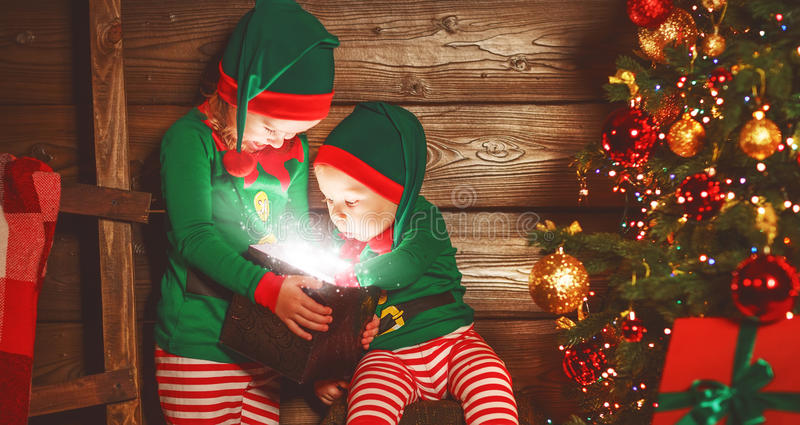happy children brother and sister elf, helper of Santa with Christmas magic gifts stock photos