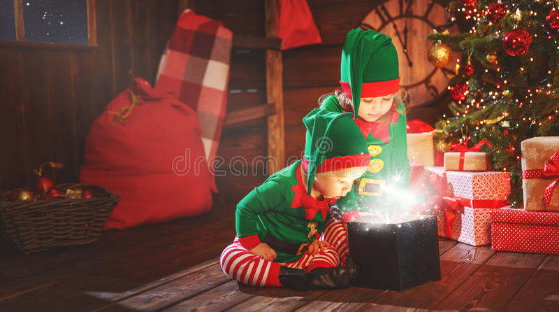 Happy children brother and sister elf, helper of Santa with Christmas magic gifts. Happy children brother and sister elf, helper of Santa with a Christmas magic royalty free stock photo