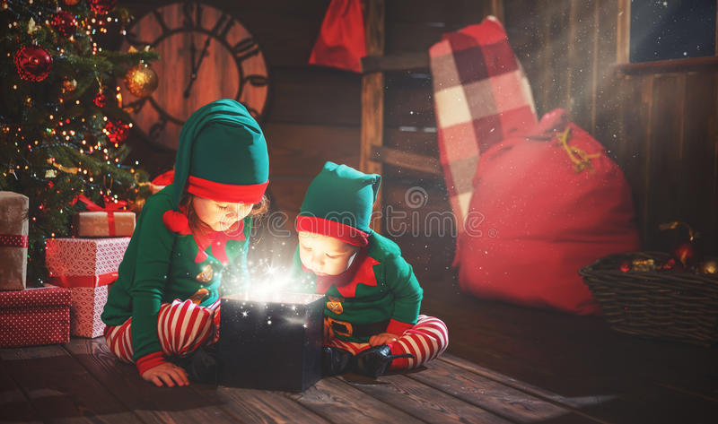 Happy children brother and sister elf, helper of Santa with Christmas magic gifts. Happy children brother and sister elf, helper of Santa with a Christmas magic stock image