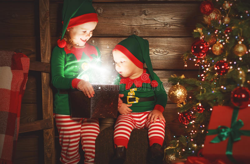 happy children brother and sister elf, helper of Santa with Christmas magic gifts stock photography