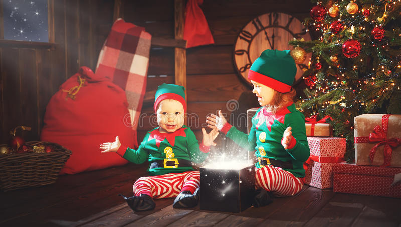 happy children brother and sister elf, helper of Santa with Christmas magic gifts royalty free stock image