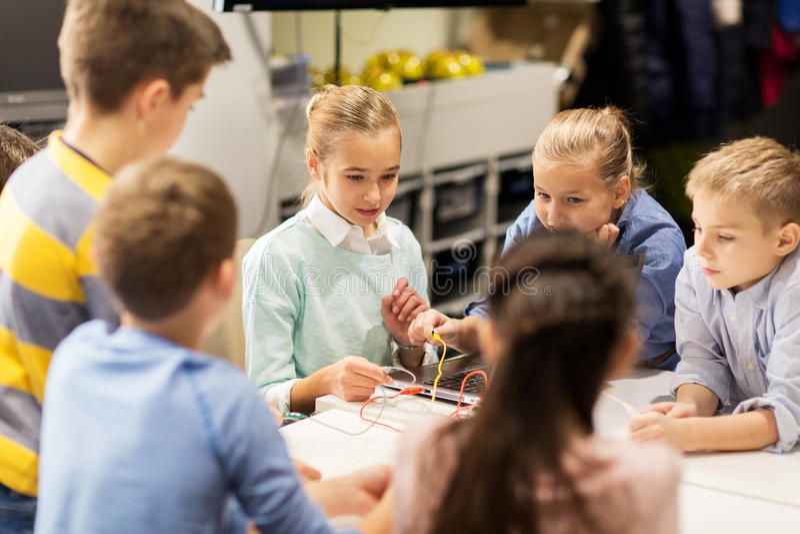 Happy children building robots at robotics school stock photos