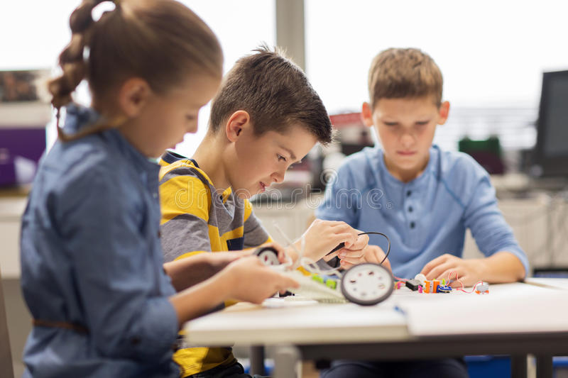 Happy children building robots at robotics school. Education, children, technology, science and people concept - group of happy kids building robots at robotics stock photography