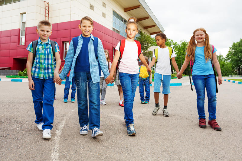 Happy children carry rucksacks, walk near school stock image