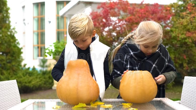 Happy children carving pumpkin jack-o-lantern, preparing for Halloween party. Stock photo royalty free stock photo