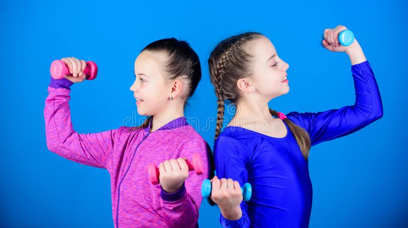 Happy children coach with barbell. Fitness diet for energy health. workout of small girls hold dumbbell. weight lifting. For muscules. Childhood activity. Sport stock image