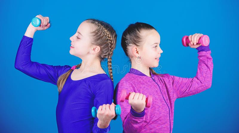 Happy children coach with barbell. Fitness diet for energy health. workout of small girls hold dumbbell. weight lifting. For muscules. Childhood activity. Sport stock photography