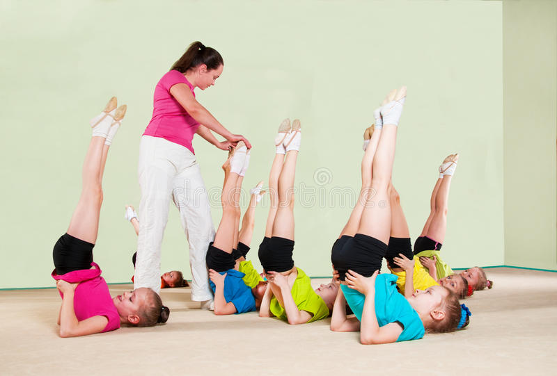 Happy children with coach in gym royalty free stock image