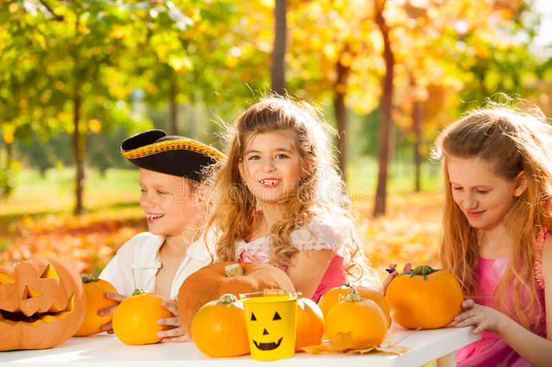 Happy children in costumes craft Halloween pumpkin stock photo