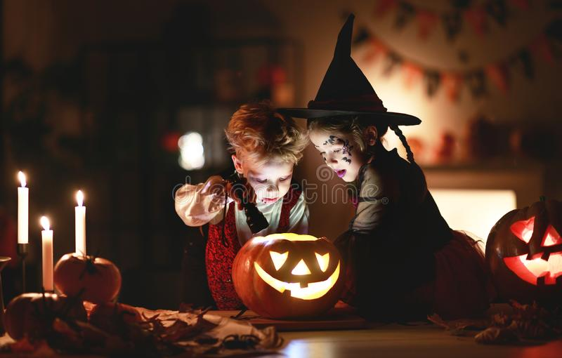 Happy children in costumes of witch and vampire in a dark house in halloween. Happy children in costumes of witch and vampire  in a dark house in   holiday stock photos